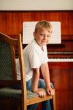Den lilla lyckliga pojken spelar pianot royaltyfri bild