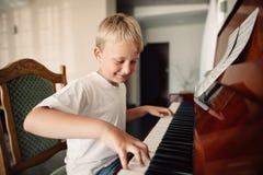 Den lilla lyckliga pojken spelar pianot fotografering för bildbyråer