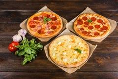 Den lilla mini- pizzakortkortet, miniatyr på bakningpapper på ett mörker uppvaktar arkivbilder