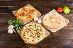 Den lilla mini- pizzakortkortet, miniatyr på bakningpapper på ett mörker uppvaktar royaltyfri foto