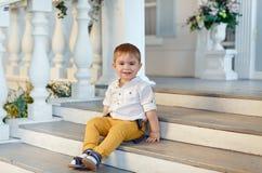 Den lilla mycket gulliga charmiga pojken i gul byxa sitter på staen arkivbilder