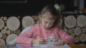 Den lilla nätta flickan drar med kulöra markörer på tabellen i rum lager videofilmer