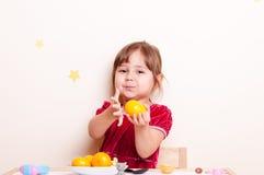 Den lilla nätta flickan ger mandarinen Arkivfoto