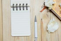 Den lilla notepaden för papper för anmärkningsboken för att skriva information med pennan, blyertspennan, boken och skrynkligt pa Royaltyfria Bilder