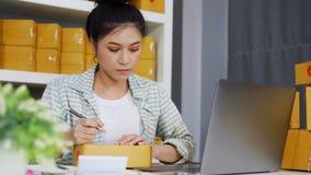 Den lilla online-företagsägaren, kvinnan som arbetar med bärbara datorn, förbereder jordlottaskar för levererar lager videofilmer