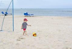Den lilla pojken önskar att slåss av en fotbollboll som spelar fotboll på strandsanden Royaltyfri Fotografi