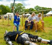 Den lilla pojken besegrar den stora riddaren Royaltyfri Foto