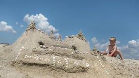 Den lilla pojken byggde en stor sandslott arkivfoto