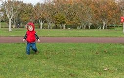 Den lilla pojken i spring för röd överkant parkerar in Fotografering för Bildbyråer