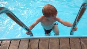 Den lilla pojken klättrar trappan från vattnet i pöl arkivfilmer