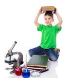 Den lilla pojken rymmer en stor bok på hans huvud royaltyfri fotografi