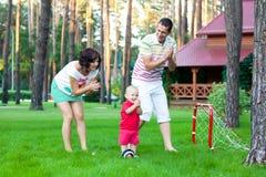 Den lilla pojken spelar fotboll med föräldrar Royaltyfri Bild