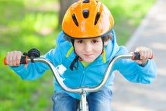 Den lilla pojkeritten en cykel arkivfoton