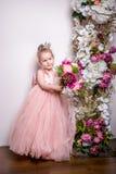 Den lilla prinsessan i en härlig rosa färg klär håll en bukett av pioner, magnolian, bär och grönska på bakgrunden av en fl royaltyfri fotografi