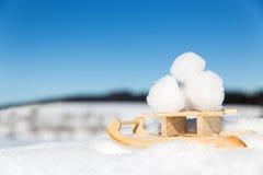 Den lilla pulkan med kastar snöboll i snön, blå himmel arkivfoton