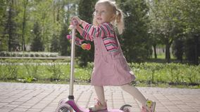 Den lilla roliga flickan i rosa klänning som rider en sparkcykel i, parkerar r Aktiv livsstil, fritid stock video