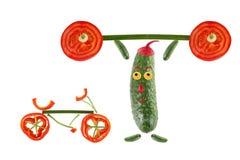 Den lilla roliga gurkan lyfter stången bredvid den står en bicycl Royaltyfri Bild