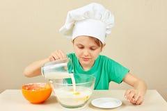 Den lilla roliga kocken häller mjölkar för att baka kakan Royaltyfri Bild