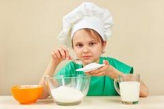Den lilla roliga kocken häller socker för att baka kakan Royaltyfri Fotografi