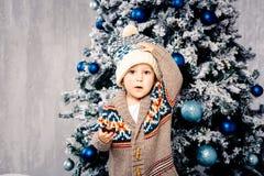 Den lilla roliga pojken i woolen tröja för huvudbonad och för kropp äter chokladsötsaker på bakgrund av en julgran på helgdagsaft royaltyfri foto