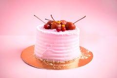 Den lilla runda rosa födelsedagkakan med mastix och dekoren bär frukt arkivfoto