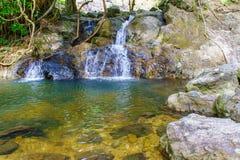 Den lilla Sarika vattenfallet i litet vaggar sjön runt om skog på den Khao Yai nationalparken Royaltyfria Foton