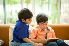 Den lilla siblingpojken som spelar leken på mobil inhyser tillsammans, vardagsrum Royaltyfria Bilder