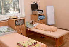 Den lilla sjuka flickan ligger på en soffa i en physiotherapeutic offi Fotografering för Bildbyråer