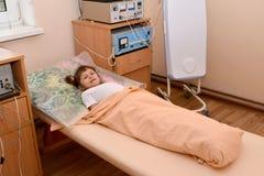 Den lilla sjuka flickan ligger på en soffa i en physiotherapeutic offi Arkivbild