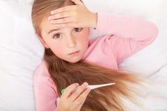 Den lilla sjuka flickan sitter på en vit soffa som slås in i en halsduk henne royaltyfri fotografi