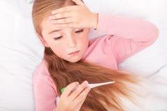 Den lilla sjuka flickan sitter på en vit soffa som slås in i en halsduk henne arkivfoto