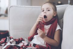 Den lilla sjuka flickan sitter på en vit soffa som slås in i en röd halsduk Hon plaskar hennes hals med en medicinsk sprej royaltyfri bild