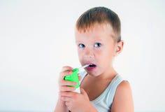 Den lilla sjuka pojken använde medicinsk sprej för andedräkt pys som använder hans astmapump Använd en sprej för allergier Gullig Royaltyfri Foto