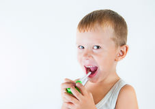 Den lilla sjuka pojken använde medicinsk sprej för andedräkt pys som använder hans astmapump Använd en sprej för allergier Gullig Arkivfoton