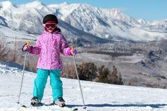 Den lilla skidåkareflickan på ett berg skidar Arkivfoto
