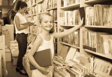 Den lilla skolflickan i bok shoppar Royaltyfri Bild