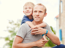 Den lilla sonen kramar hans fader på hals Royaltyfri Fotografi
