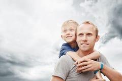 Den lilla sonen kramar hans fader på hals med stor cloudscape Royaltyfri Foto