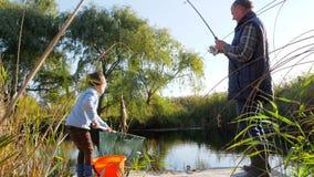 Den lilla sonsonen med morfadern fiskar i sjön i trevligt väder bland träd och gräs stock video