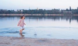 Den lilla stilfulla flickan går på banken av sjön Barnet hoppar på vatten arkivfoton