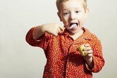 Den lilla stiliga pojken äter Yogurt.Child med skeden Arkivbilder