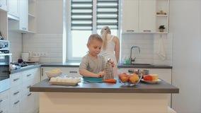 Den lilla stiliga pojken gnider en morot på tabellen En ung härlig caucasian moder med kocken för vitt hår och soni a lager videofilmer