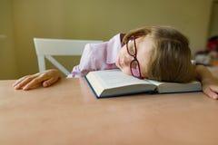 Den lilla studenten i exponeringsglas sover på ett skrivbord, hennes huvud på en öppen bok Skola, utbildning, kunskap och barn royaltyfria foton