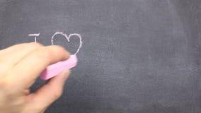 Den lilla svart tavla med texten älskar jag dig som är skriftlig på den i krita stock video