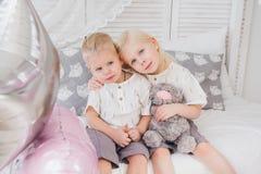 Den lilla systern och brodern sitter på sängen arkivbild