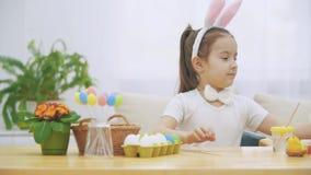 Den lilla trevliga flickan klättrar in i en mjuk stol och spelar med kaninen Hon sitter ner på tabellen med påsk arkivfilmer