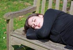 Den lilla tystnaden ta sig en tupplur på en bänk Fotografering för Bildbyråer