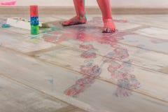 Den lilla ungen är playind med målarfärger arkivfoton