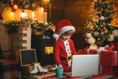 Den lilla ungen bär jultomtenkläder vid hans bärbar dator Julfilial och klockor Spisbakgrund Julmarknad i Munich, Tyskland arkivfoton