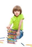 Den lilla ungen har byggt ett torn av blyertspennor royaltyfri foto